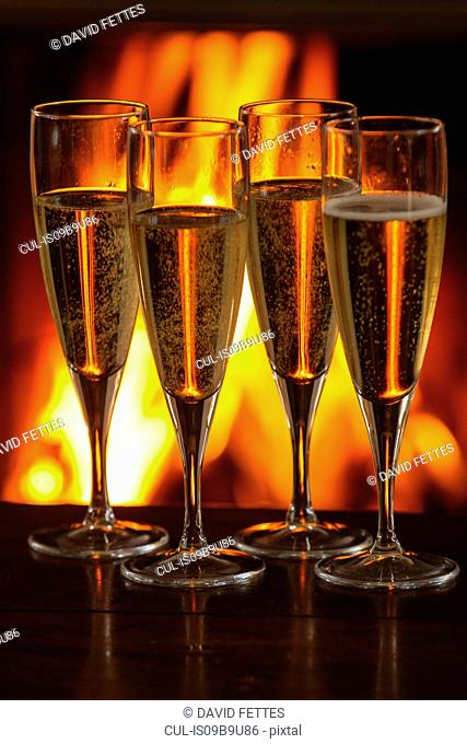 Four filled champagne glasses on table in front of burning fire