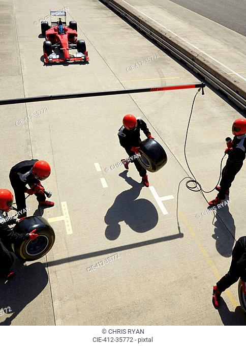 Pit crew preparing tires for nearing formula one race car in pit lane