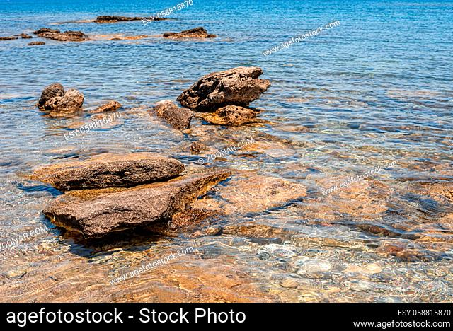View of the transparent blue sea with big rocks and stones at the bottom