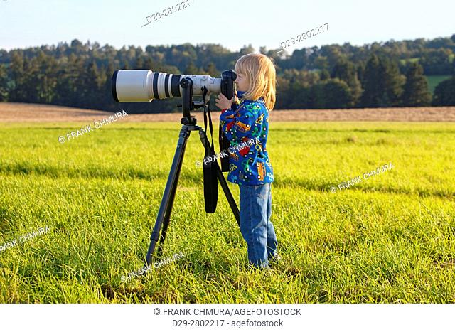 boy looking through super telephoto lens on digital camera