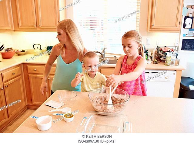 Family preparing batter in mixing bowl