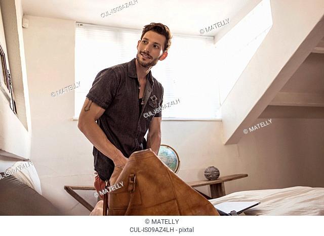 Man in bedroom packing bag