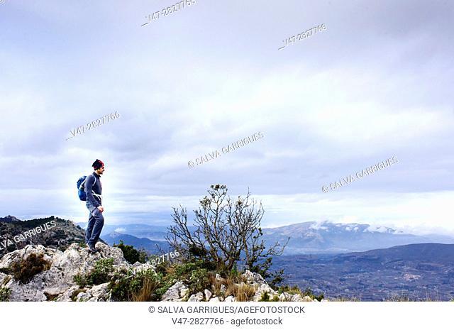 ountaineer on top of the mountain in Quatretondeta, Alicante, Valencia, Spain