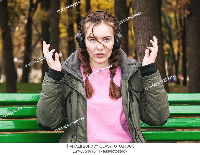 Surprised young girl with headphones. A teenage girl on a park bench in autumn