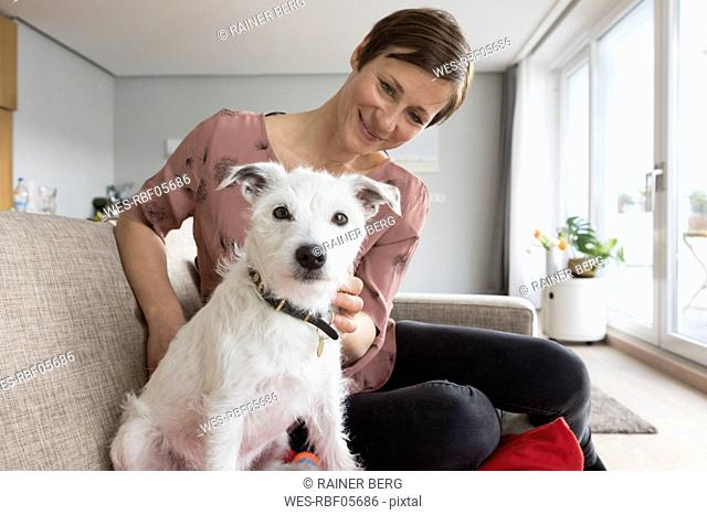 Woman and her dog sitting together on the couch