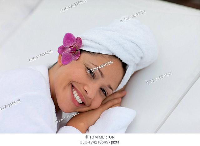 Woman laying on lounge chair with head wrapped in towel