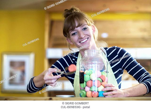 Portrait of young woman in food shop, taking sweet food from jar