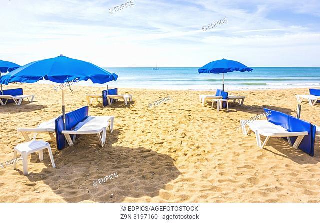 blue umbrellas and sun chairs at deserted beach, albufeira, algarve, portugal