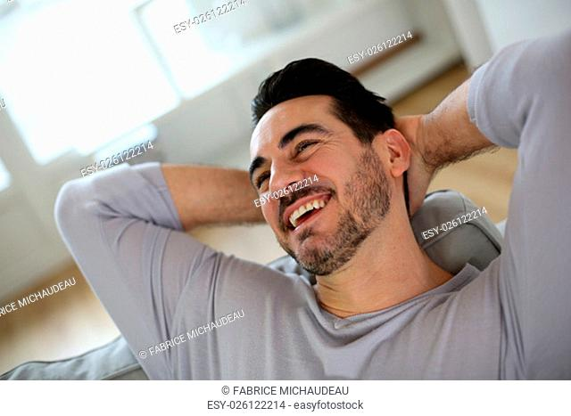 Relaxed man stretching arms behind head