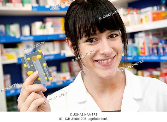 This picture shows a young caucasian woman with brown hair pharmacist holding a belgian Social Security Card called Carte SIS / SIS-kaart in her hand