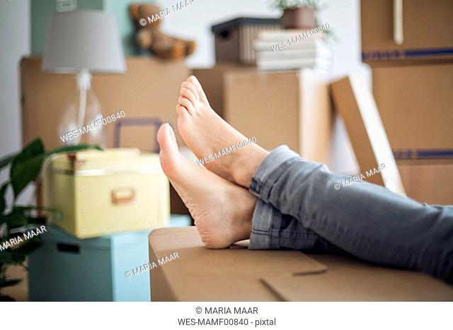 Bare feet of woman relaxing surrounded by cardboard boxes in a new home