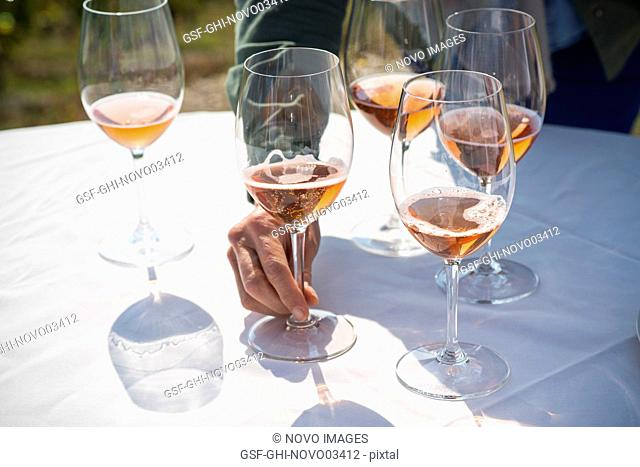 Mid-Adult Woman Reaching for Glass of Rose Wine