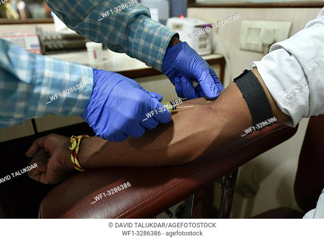 Guwahati, Assam, India. April 6, 2019. Laboratory technician taking blood samples from a patient in the eve of World Health Day in Guwahati