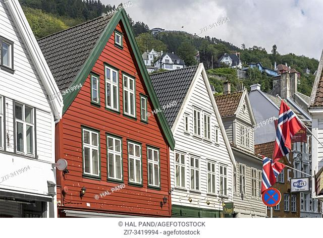 BERGEN, NORWAY - July 19 2019: touristic town cityscape with picturesque houses facades and Norwegian flags, shot under bright summer light on july 19