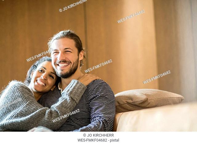 Portrait of happy young couple sitting on the couch