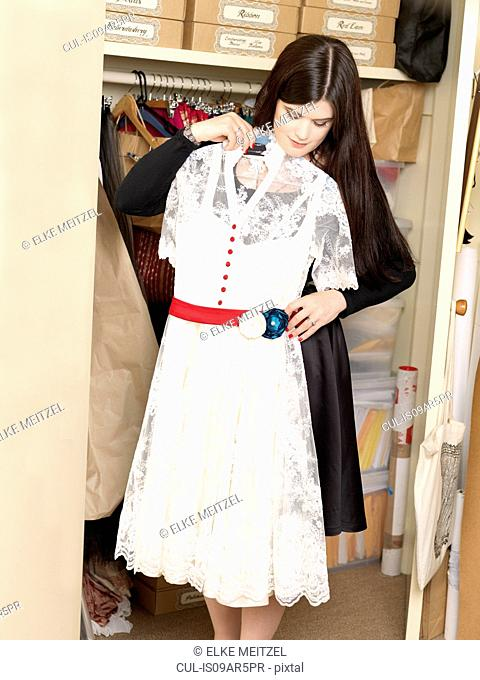 Corset maker showing off white dress