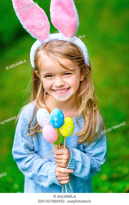 Beautiful smiling little girl with long blond hair wearing pink rabbit or bunny ears and blue knitted dress and holding bunch of painted colour eggs on sunny...