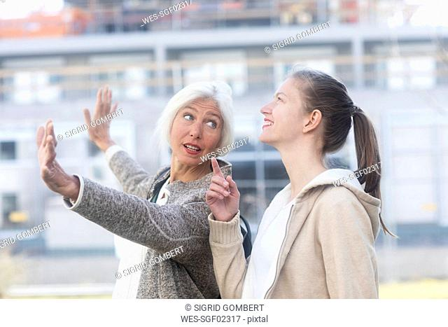 Portrait of mature woman explaining something to her adult daughter