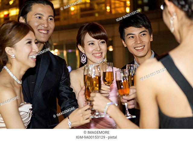Friends holding wineglass and looking away with smile together