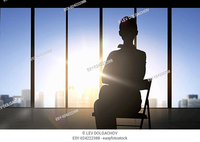 business and people concept - silhouette of woman sitting on chair over office window background