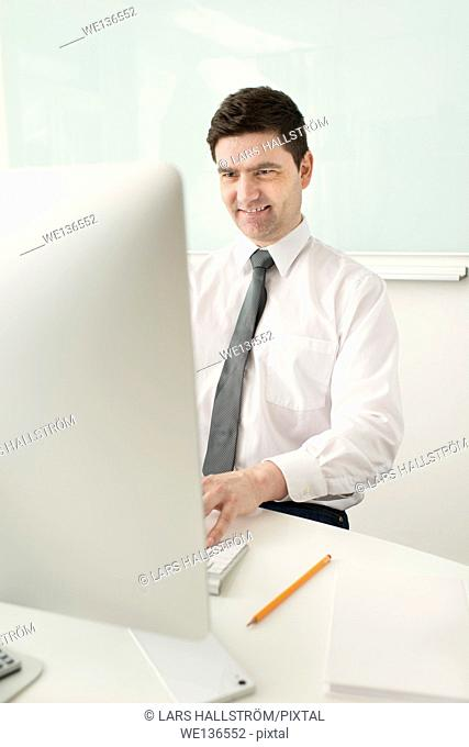 Smiling businessman sitting by desk, working with computer in office