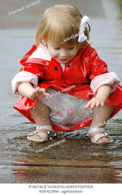 Close up of toddler girl playing in puddle