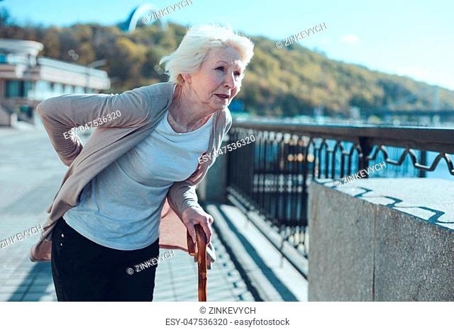 Physically exhausted elderly woman leaning on a cane and looking into vacancy while struggling from a physical discomfort in a low back zone