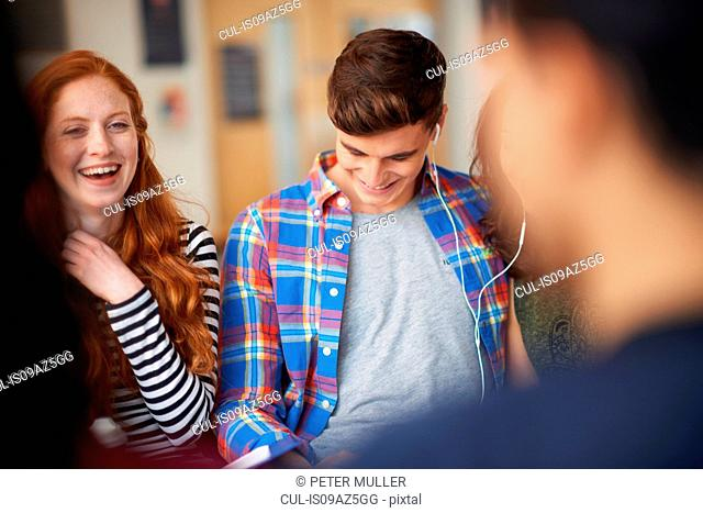 Young male and female students laughing in common room