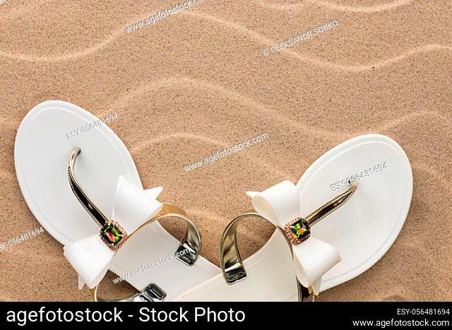 White flip flops on the sand of the beach. Concept of rest. View from above