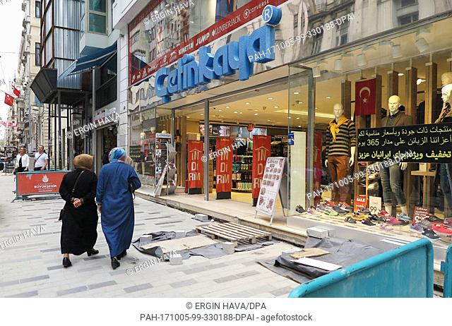 View of stores on the Istiklal caddesi in the popular district Beyoglu advertising in Arabic, Persian and English language in Istanbul, Turkey