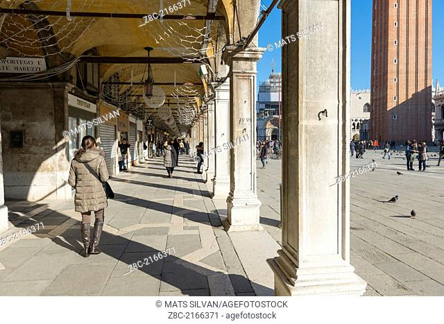 People walking under the archway and on piazza San Marco in Venice Italy