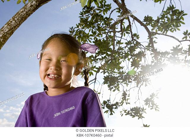 Portrait of a Asian girl sitting under a tree