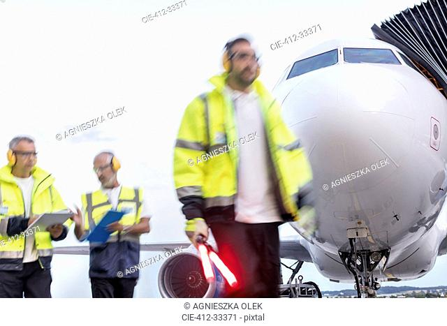 Air traffic controllers walking in front of airplane on airport tarmac