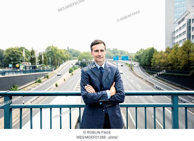 Portrait of confident businessman standing on motorway bridge
