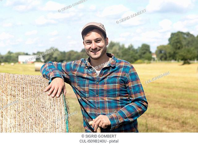 Farmer leaning against hay bale looking at camera smiling