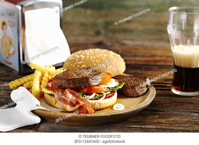 Burger with fried fillet steaks, bacon, ketchup, french fries and cola