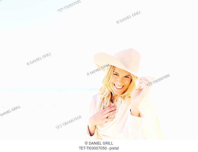 Portrait of woman in cowboy hat on beach
