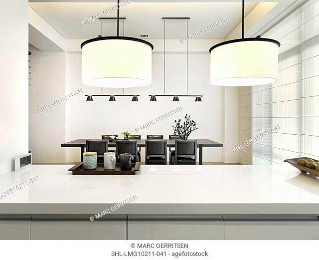 View over white countertop to dining room in modern home