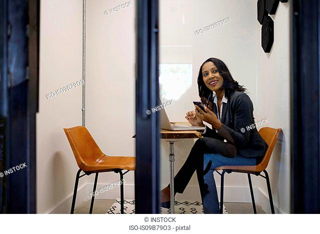 Businesswoman sitting in office, using laptop, holding smartphone, smiling