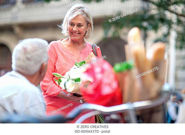 Woman showing bouquet to senior man in city
