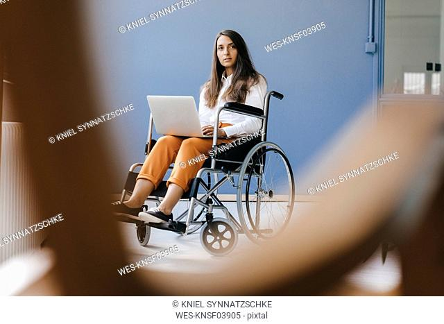 Young handicapped woman sitting in wheelchair, using laptop