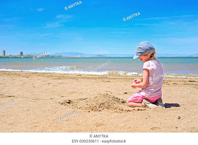 Little girl sitting and playing on the sandy Mar Menor beach, Spain