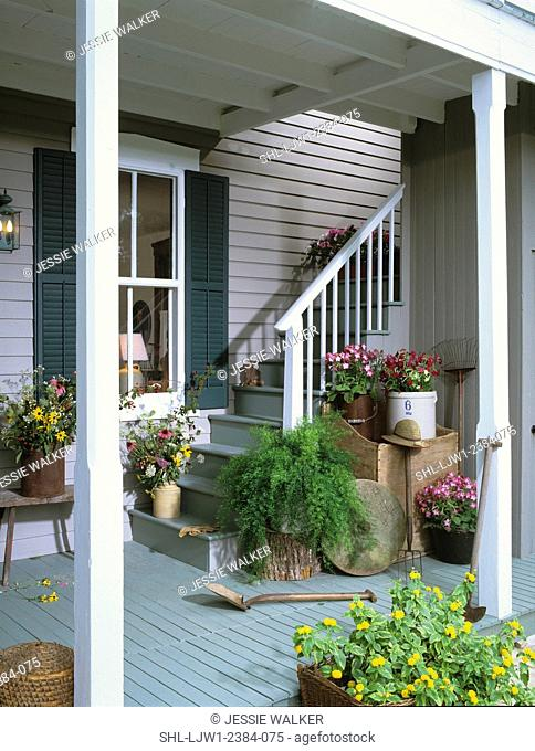 PORCH: Stairway from a covered porch area, green shutters, clapboard, various containers filled with flowers, antique wood box, crocks, garden tools
