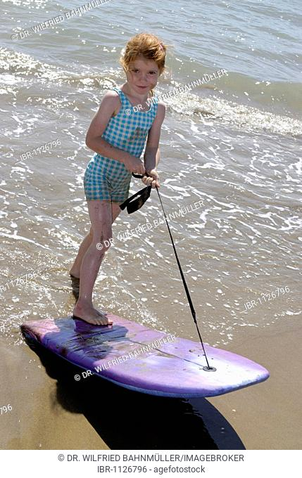 Child with surf board, boogy board, at the beach at the sea