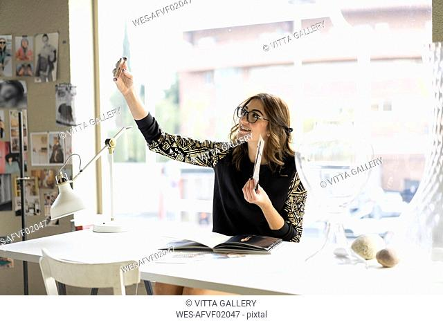 Smiling young designer taking selfie with smartphone in an atelier