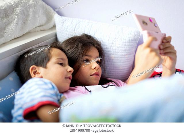 Children playing computer games in bed