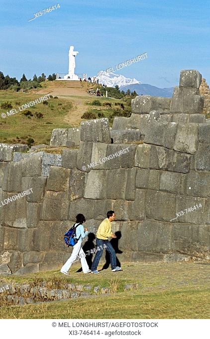 Sacsayhuaman Inca ruins, tourists, statue of Jesus Christ, and Ausangate Mountain behind, near Cusco, Peru