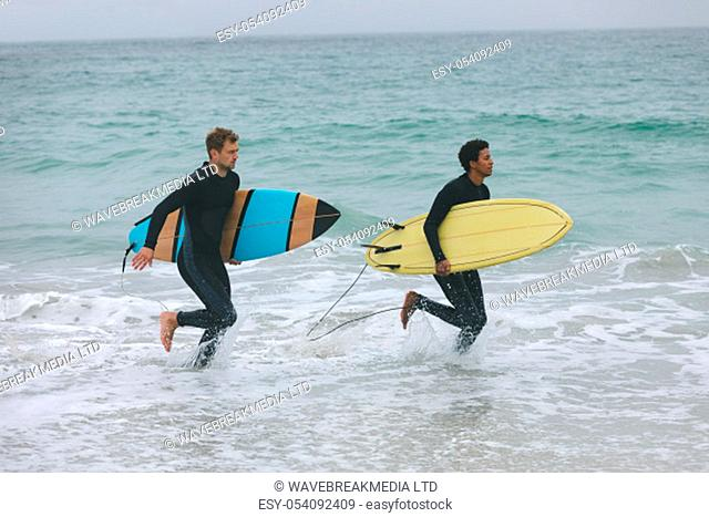 Side view of young multi-ethnic male friends running on beach while holding surfboards