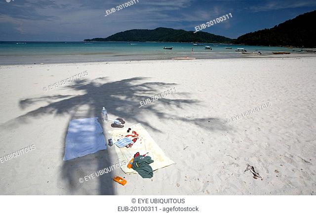 Beach scene with towels sun cream sunglasses cigarettes sandals and book under the shade of a coconut tree