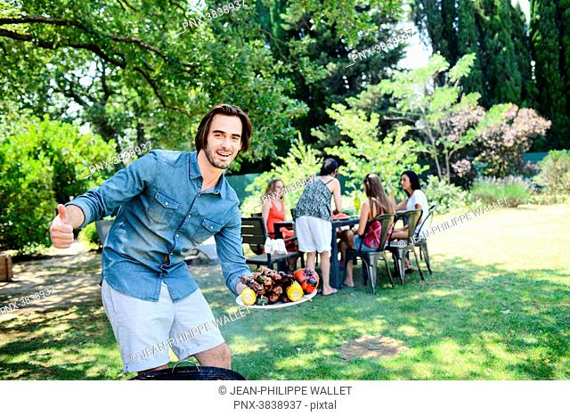 Handsome young man showing grilled meat in barbecue party outdoor in the garden during summer holiday